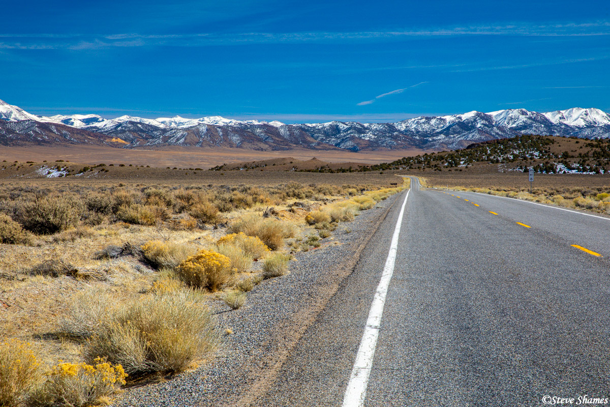 On the road that leads to Gabbs, a very Nevada scene -- a lonely road in the middle of nowhere with snow covered mountains in...