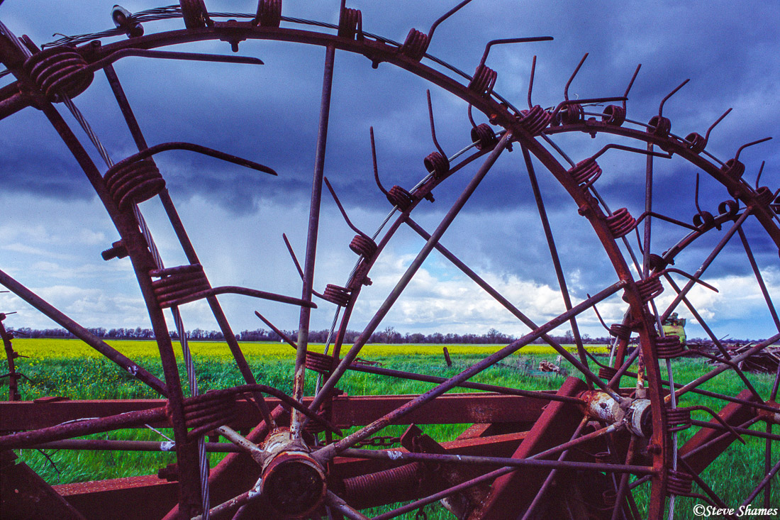 sacramento valley, california, stormy skies, old rusting farm equipment, photo